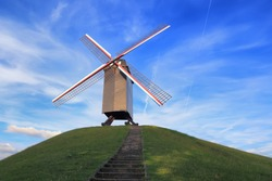 Windmill on green hill on a sunny day. Retro windmill on blue sky background. Landmark of Bruges.