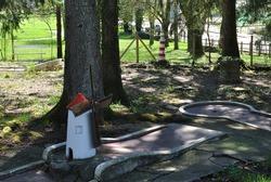 Windmill on Old Outdoor Miniature Golf Course beneath Trees