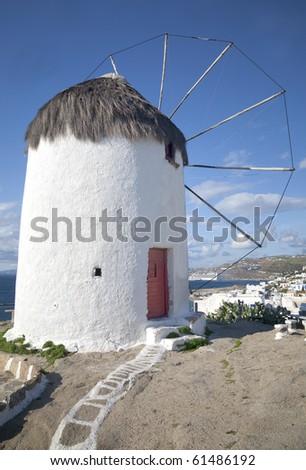 Windmill overlooking a village on the island of Mykonos, Greece.