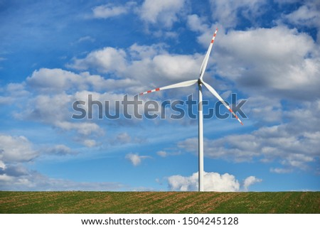 Windmill producing ecological energy on a green field against the sky with clouds