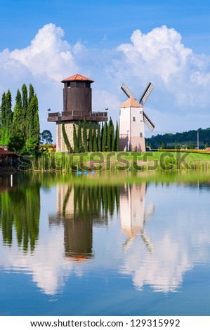 windmill reflection on the water with blue sky background