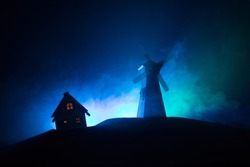 Windmill silhouette standing on hill against the night sky. Night decor with old windmill on hill with horror toned foggy background with light. Horror concept