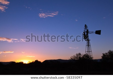 Windmill spinning fast at sunset with lovely orange colours in the Karoo