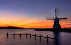 Windmill surrounded by colorful sunset
