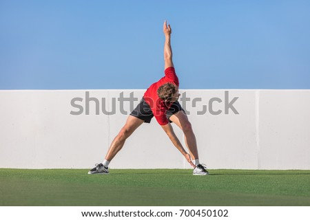 Windmill toe touch stretch dynamic stretching man standing training flexibility with back spinal twist exercise. Fitness athlete doing running warm up in summer park or home garden outdoors.