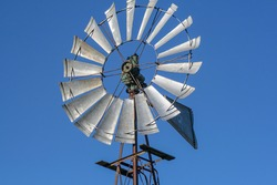 Windmill, with up to aluminum, behind the blue sky.