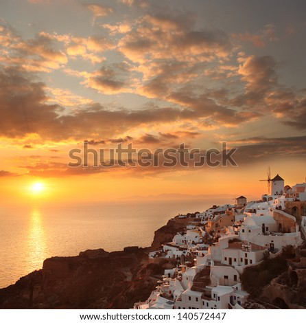 Windmills against colorful sunset in  Santorini, Greece