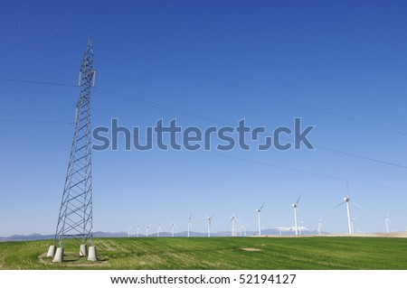 windmills aligned and high voltage electrical line with a clear blue sky