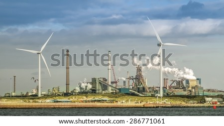 Windmills and old industrial area at the sea side. New and old technologies together shows a contrast in North Europe
