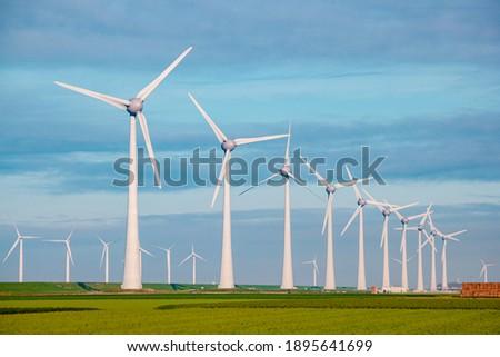 Windmills for electric power production Netherlands Flevoland, Wind turbines farm in sea, windmill farm producing green energy. Netherlands Сток-фото ©