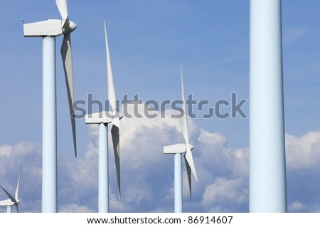 windmills for electric power production with cloudy sky
