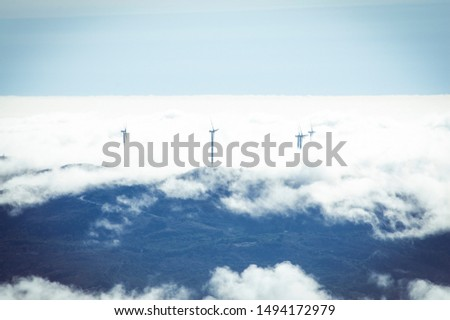 Windmills generating electricity in the clouds / alternative energy / beautiful view. #1494172979