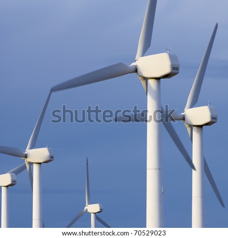windmills group for energy production with cloudy sky
