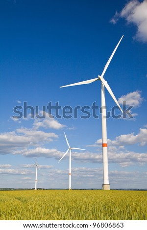 Windmills in a field of crop with blue sunny sky