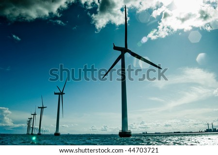 Windmills in a row against sun