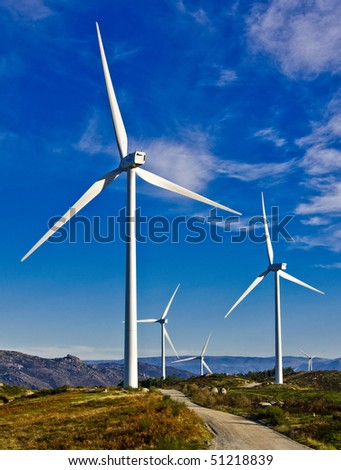 windmills in the top of a montain with blue sky and clouds, alternative energy source