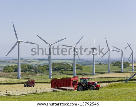 Windmills in windfarm with tractors working in foreground