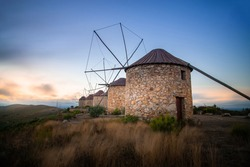Windmills on top of a mountain at sunset. Photography made in Portugal.