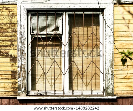 Window and facade of the old house with peeling paint