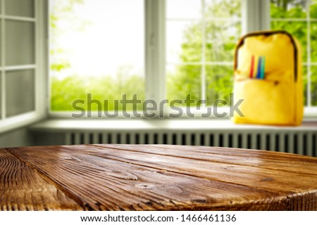 Window and wooden table top background with a yellow schoolbag on a windowsill. Empty space for products and decoration.