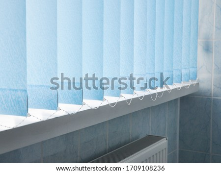 Window blue cotton blinds, vertical louvers, swings is a good window covering in offices. Stock photo ©