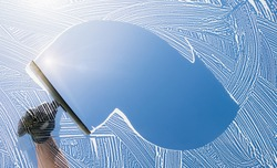 window cleaner cleaning window with squeegee and wiper on a sunny day