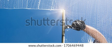 Window cleaner cleans window with foam and puller, banner size, banner size, panorama, with copyspace for your individual text. Foto d'archivio ©