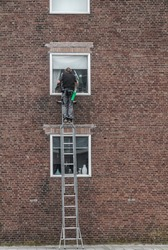 window cleaner standing high on a ladder to wash the windows of an apartment building