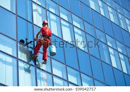window cleaner working on a glass facade modern skyscraper