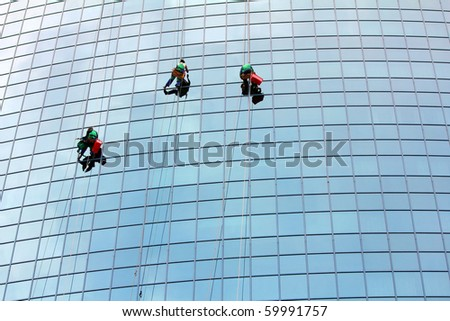 window cleaners hanging on rope at work on skyscraper