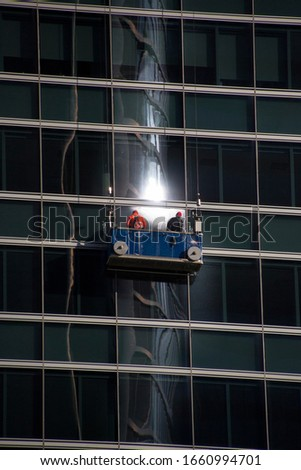 Window cleaners on its platform with different reflections, in Madrid, by Fermín Tamames Stok fotoğraf ©