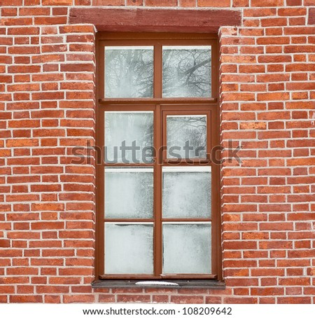 Window covered with frost-work in brick wall