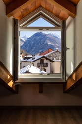 Window detail with a view of Swiss snow-capped mountains. Nobody inside