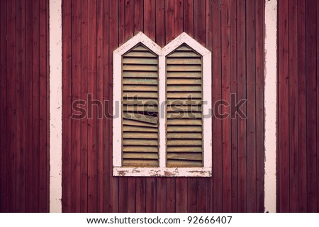 Window frame with shutters on rustic red wooden wall