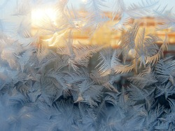 Window glass covered in frost in the afternoon sunlight reflected from another house. Blue sky, frost sparkling in the orange sunlight. Complicated patterns New Year and Christmas winter background.