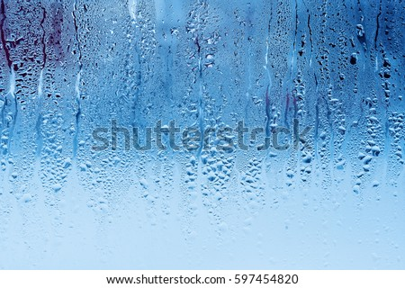 Window glass with condensation, high humidity. Cool color tones on the image