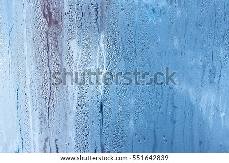 Window glass with condensation, high humidity in the room, large water droplets, cold tone