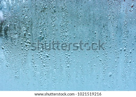 Window glass with condensation high humidity , large droplets flow down , cold tone. Natural water drop background