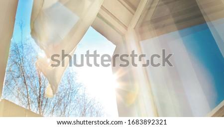 Window is open wind blows curtain sun shining through window blue sky background