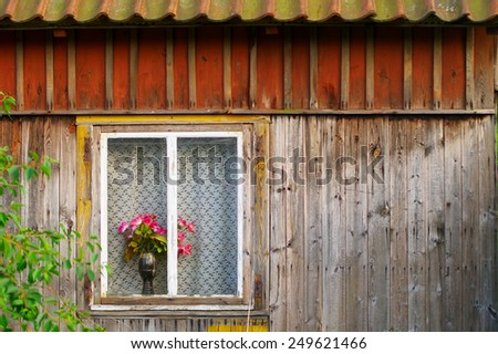Window of an old wooden cottage with red roses in a vase. Pomerania, Poland.