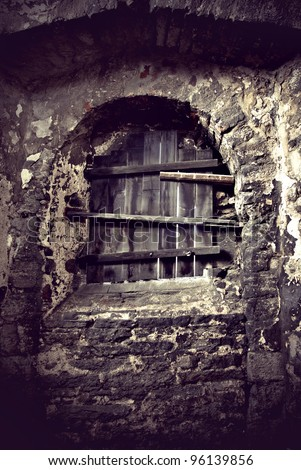 Window of ancient castle sealed with planks