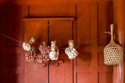 Window of ancient times in Thailand have a garlic, shallots and round bamboo basket hanging