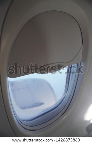 Window of the plane is closed in flight. Theme vacations for the travel agency. Stock photo