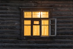 Window of the wooden ancient house at night time.