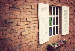 Window on a red brick wall with vintage tone