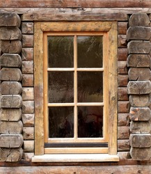 Window on an old wooden building. Decoration inside the glasses.