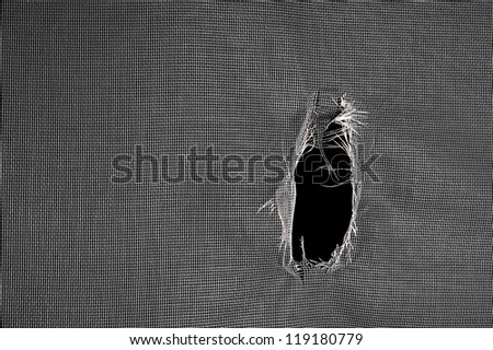 Window screen torn with a big hole against a black background.