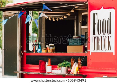 Window selling a red food truck with pennants