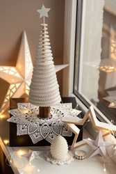 Window sill decorated with modern Christmas tree shaped wooden decoration on a handmade crochet doily, several star shaped paper and wood decorations and fairy lights