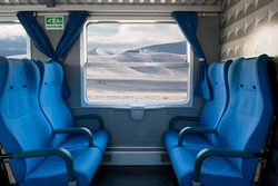 Window train with snow landscape and empty seats.